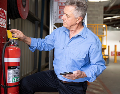 Fire technician maintaining a fire extinguisher using FireMate mobile app